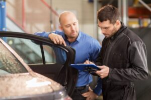 car repair estimate done by auto mechanic and customer at car shop